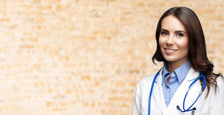 Photo for Portrait picture of happy smiling female doctor in white uniform coat and stethoscope, over loft style wall background. Healthcare, medical, medicine specialist - concept. Copy space. - Royalty Free Image