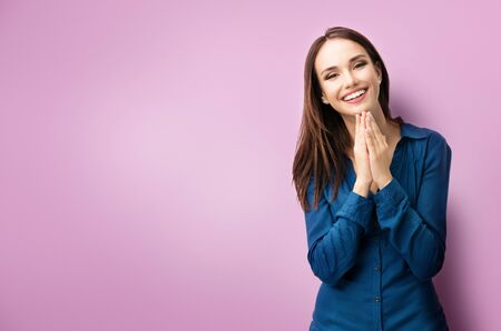 Photo pour Portrait of happy gesturing dark haired woman in casual smart blue clothing, pressing palms together, over purple background, with copyspace for slogan, advertising or text message - image libre de droit