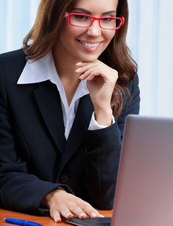 Photo pour Portrait image of smiling businesswoman in black confident style suit and red eye glasses, working with laptop computer at office. Success in business, job and education concept shot. - image libre de droit
