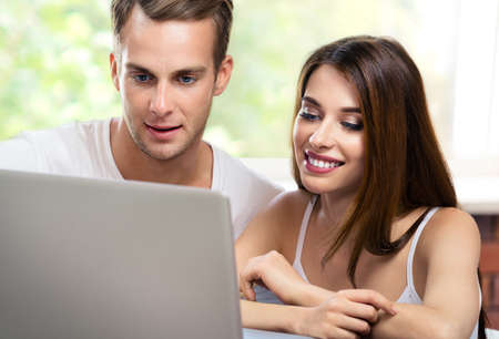 Photo pour Image of happy smiling couple using laptop at home. Internet, shopping, online store, love, relationship concept - young man and woman with domestic computer together. - image libre de droit