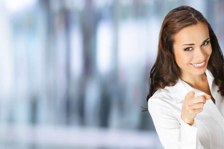 Photo for What about You? Happy smiling woman in confident clothing pointing finger at viewer, copy space. Business concept. Blurred modern office interior background. Brunette businesswoman, indoors. - Royalty Free Image