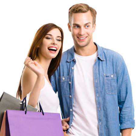 Photo pour Happy couple with shopping bags, standing close to each other with smile. Caucasian models in love, holiday sales, shop, retail, consumer concept, isolated on white background. Square. - image libre de droit