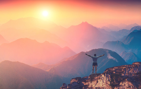Man with raised hands standing on a mountain top and welcome sunrise in a Carpathian mountains