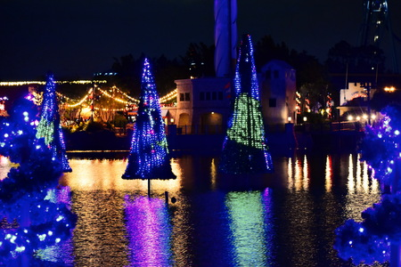 Orlando, Florida. November 21, 2018. Colorful illuminated Christmas trees and their reflection in the lake at night in International Drive area