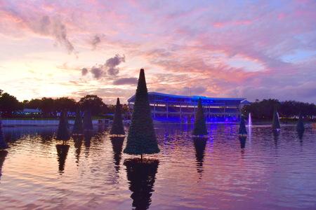 Orlando, Florida; November 15, 2018. Christmas Tree over the lake and colorful stadium on sunset background in International Drive area.