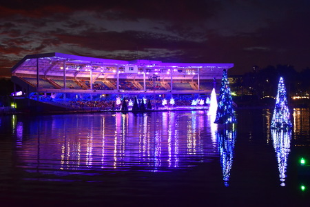 Orlando, Florida; November 23, 2018. Illuminated Christmas Tree over the lake and colorful stadium on sunset background in International Drive area.