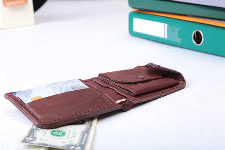 leather wallet with credit cards, Folder file, and note on the desk. blurred background.