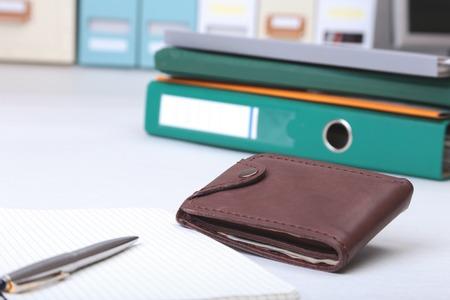 Folder file, note and wallet on the desk. blurred background.