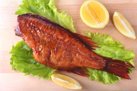 Smoked fish and lemon on green lettuce leaves on Wooden cutting board isolated on white background.
