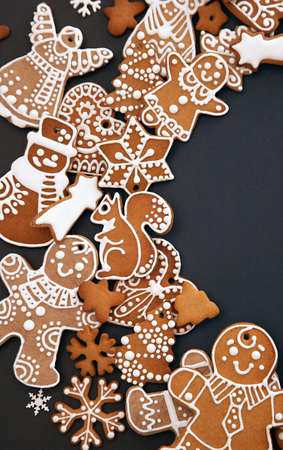 Photo pour Christmas gingerbread cookies with icing and confectionery mastic snowflakes on black background, view from above. Holiday food, homemade baking, Christmas and New Year traditions. - image libre de droit