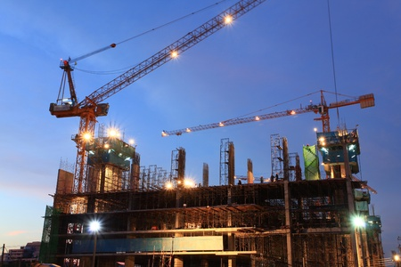 Scaffolding construction site at dusk with moving crane