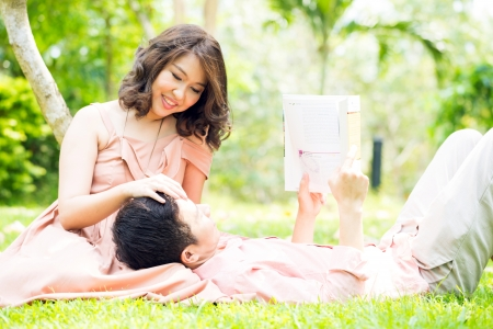 Couple relaxing in the garden, young man reading a book and lying on his girlfriend lapの写真素材