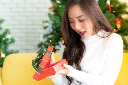 Photo pour beautiful happy asian girl opening christmas present gift box for Christmas holiday season greeting. - image libre de droit