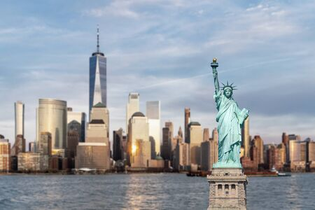Statue of Liberty with background of New York city Manhattan skyline cityscape at sunset from New Jersey.