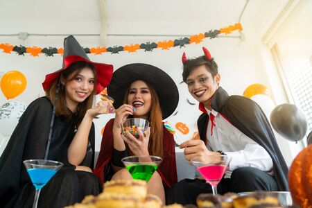 Photo pour Group of young adult and teenager people celebrating a Halloween party carnival Festival in Halloween costumes with food and drink on table. - image libre de droit