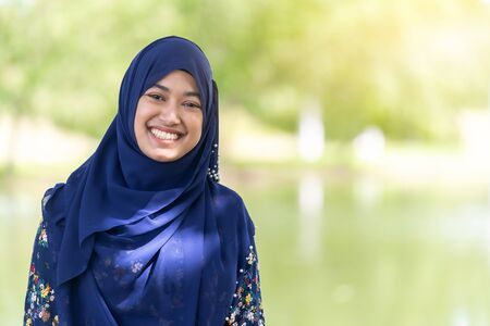 Portrait of good-looking Happy young teenager Muslim islamic asian university girl