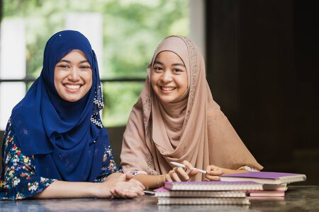 Photo pour Teenager Young Adult Asian Thai Muslim university college students reading book and using digital tablet together using for education and online education concept - image libre de droit