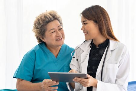 Photo pour Asian confidence doctor using digital tablet expressing health concerns with old elderly woman patient sit on wheelchair - image libre de droit
