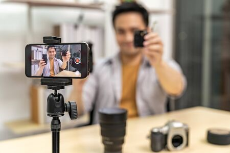 Photo for Young asian male IT vlogger and blogger live about digital camera Technology upgrand using mobile phone to recording live vlog video. Online influcencer on social media concept. Focus on camera. - Royalty Free Image