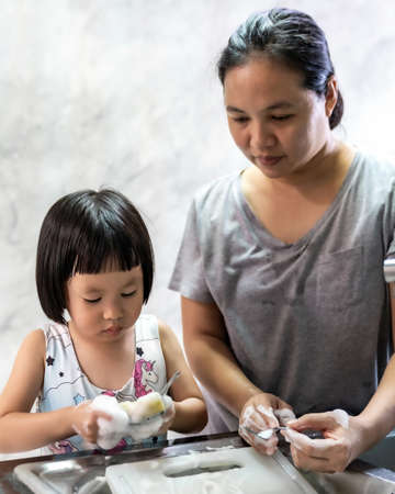 Photo for Asian girl washing dish and tableware with her mom, housework for child make executive function for kid. Houseworking for kid lifstyle and family concept. - Royalty Free Image