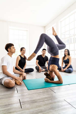Photo for Asian yoga female coach or instructor wear sportswear bra pants show student in fitness studio class  poseture of headstand pose. Yoga Practice Work out exercise and healthy lifestyle concept. - Royalty Free Image