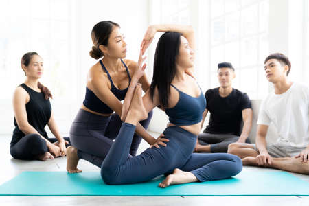 Asian people learning Yoga class in fitness club. Instructor coaching and adjust correct pose on king pigeon pose to student at front while others looking. Yoga Practice Work out lifestyle concept.