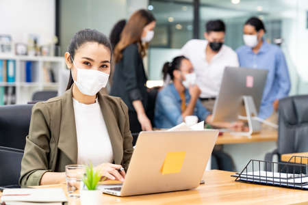 Foto für Portrait of asian office employee businesswoman wear protective face mask work in new normal office with interracial team in background as social distance practice prevent coronavirus COVID-19. - Lizenzfreies Bild