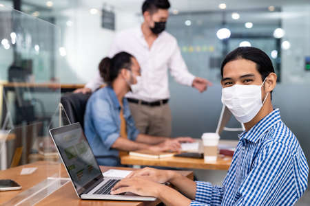 Photo pour Asian Office employee with protective face mask working in new normal office with social distance practice to his colleague in background prevent coronavirus COVID-19 spreading. - image libre de droit