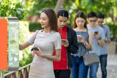 Photo pour Asian woman using kiosk of food ordering with social distance queue in line befor getting in fast food restaurant. Online technology self service new normal restaurant concept. - image libre de droit