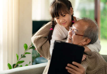 Photo pour Happy retirement elderly man sitting on sofa at living room with granddaughter using digital tablet together. Multigenerational family with technology concept. - image libre de droit