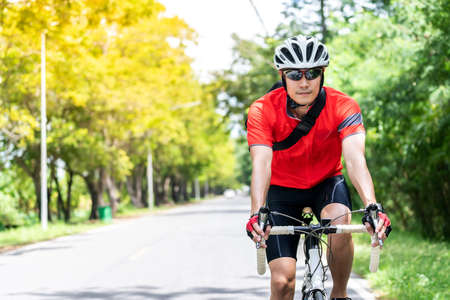Photo for Portrait of asian male cyclist in sportware shirt cycling along countryside road with green tree in background. Weekend outdoor sport athlete and fitness concept. - Royalty Free Image