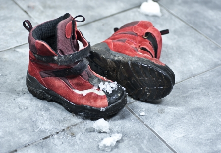 A pair of winter shoes full of snow making the entrance floor messy