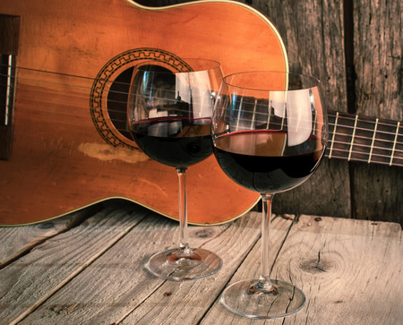 Foto de guitar and Wine on a wooden table romantic dinner background - Imagen libre de derechos