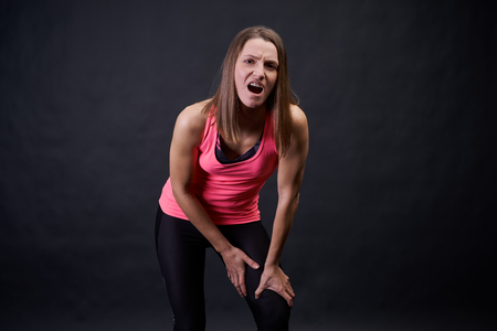 Woman athlete runner stands on an isolated black background in a pink tank top and holds the knee and thigh from severe burning pain. A beautiful blonde girl did not follow the rules of sports walking