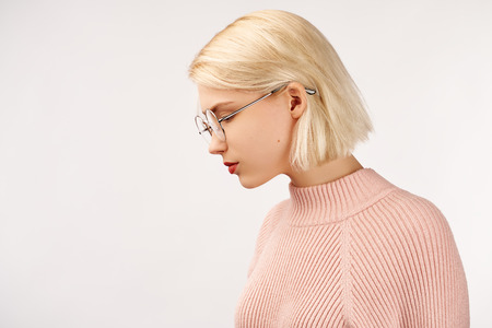 Foto de Profile of serious female with healthy pure skin, wears round glasses, has contemplative expression, isolated over white studio wall with copy space. - Imagen libre de derechos