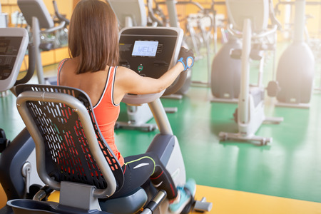 Photo pour Photo sports woman sitting on a stationary bike, doing cardio exercise, pedaling, measures the pulse. Silhouette of the back of a young girl in the gym. - image libre de droit