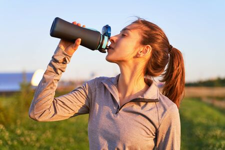 Foto de A young girl after workout drinking water - Imagen libre de derechos