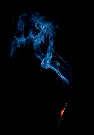 Smoke of incense stick isolated on the black background