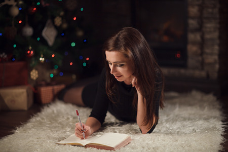 Beautiful woman writing list of wishes near christmas tree.
