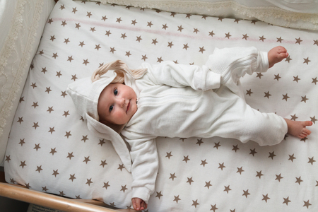 Photo pour Cute baby in the rabbit costume lying in the bed - image libre de droit