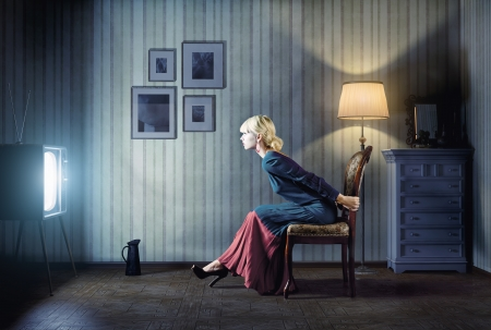 Young  woman sitting on a chair in vintage interior  and watching retro tv  She is very astonished while watching tv in dark room