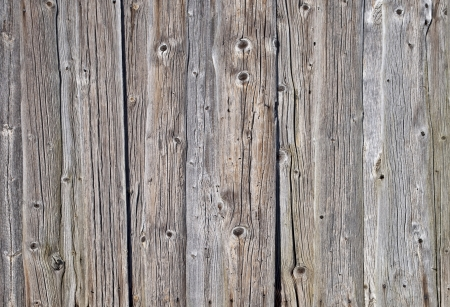 Fragment of weathered rough uncolored wooden boards background