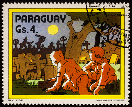 Moscow, Russia - July 30, 2017: A stamp printed in Paraguay shows Tom Sawyer and Huck Finn at the cemetery, Adventures of Tom Sawyer by Mark Twain, series International Year of Youth, circa 1985