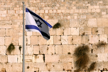 State flag of Israel against the background of the Wailing wall in Jerusalem, Israel.