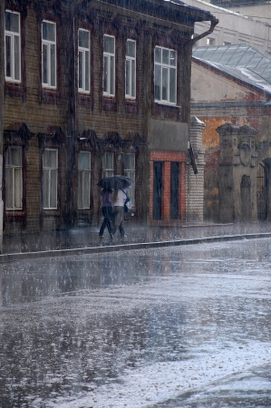 Two women walk in the rain down the street of the old Russian town