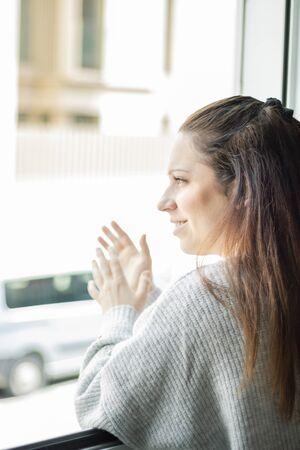 Foto de Young woman leaning out of the window applauding - Imagen libre de derechos