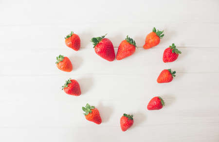 Foto de Top view of fresh strawberries on a rustic white wooden table, creating the shape of a heart, as a symbol of love. Concepts, san velentin, romantic - Imagen libre de derechos
