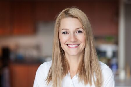 Close up Of A Smiling Caucasien blond woman in the kitchen at home