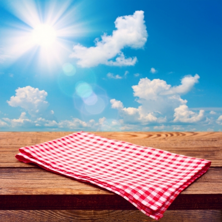 Empty wooden deck table with tablecloth for product montage. Free space for your text