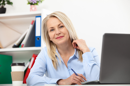 Photo pour Her job is her life. Business woman working in office with documents. Beautiful middle aged woman looking at camera with smile while siting in the office. - image libre de droit